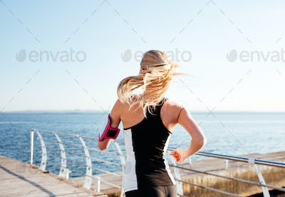 Back view of young woman exercising on the sea pier