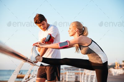 Young couple exercising and stretching muscles before sport activity