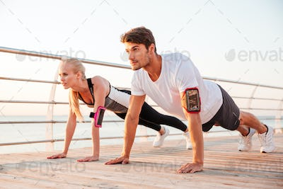 Young sports woman and man doing plank exercise together outdoors