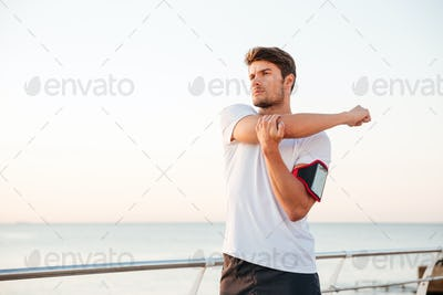 Young muscular man stretching his arms outdoors