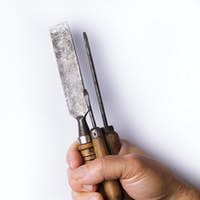Strong hand holding tools with wooden handles on white backgroun