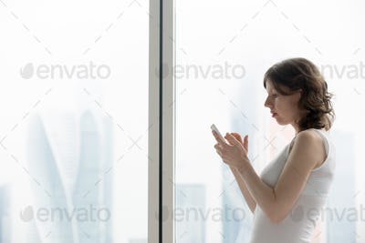 Young woman typing smartphone message
