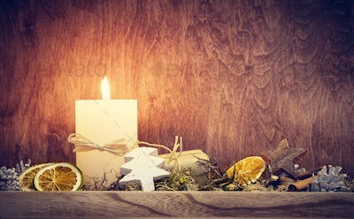Chistmas decoration with candle glowing on wooden wall background