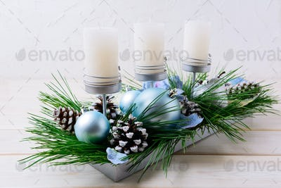 Christmas table centerpiece with candles and blue ornaments
