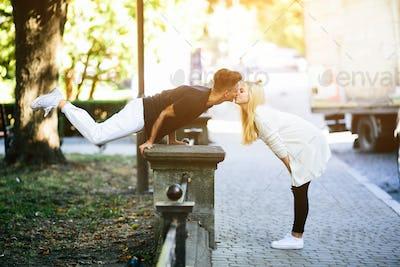 man performs an acrobatic trick near a girl