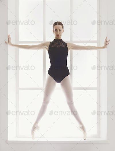 Beautiful ballerine stands in releve ballet position