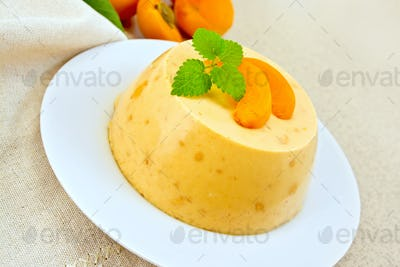 Panna cotta apricot with mint and napkin on table