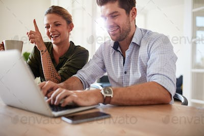 Cheerful young couple using laptop at home