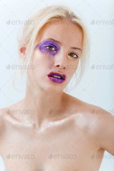 Beauty portrait of blonde young woman with stylish creative makeup