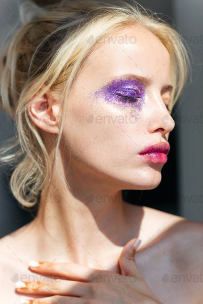 Closeup of attractive young woman with creative purple makeup