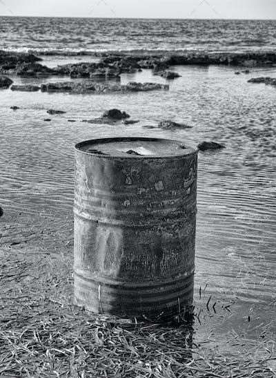 Rusty oil barrel near the shore of the sea