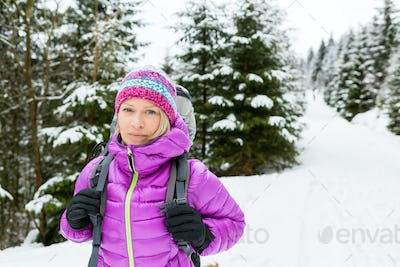 Woman hiker in winter forest with backpack