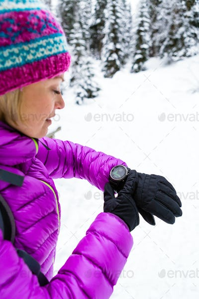 Woman hiker checking sports watch in winter woods and mountains