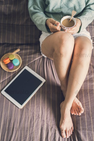 Young woman relaxing at cozy home atmosphere on the bed
