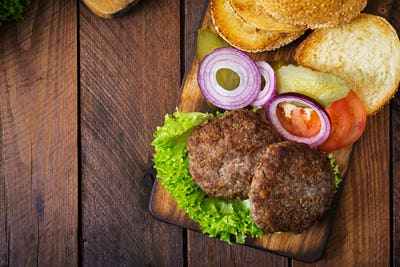 Ingredients for a sandwich - hamburger burger with beef, pickles, tomato and red onion