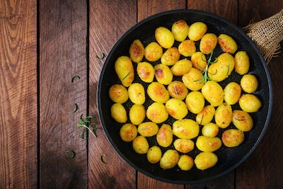 Baked potatoes with rosemary and pepper in a frying pan on wooden background. Top view