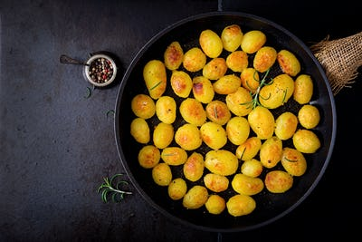 Baked potatoes with rosemary and pepper in a frying pan on black background. Top view