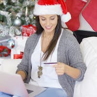 Happy young woman making online Xmas purchases