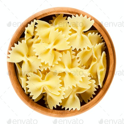 Farfalle pasta in wooden bowl over white