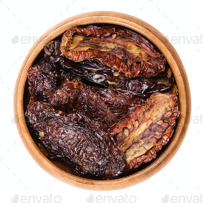 Sun dried tomatoes in a wooden bowl on white background