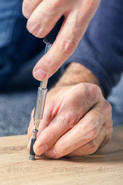 Man assembling furniture at home, hand with screwdriver