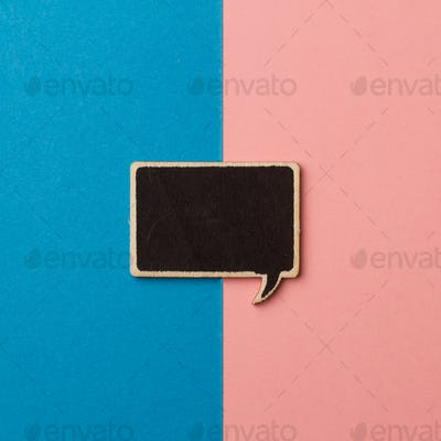 square empty chalkboard wooden speech bubble on pink and blue
