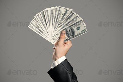 Business Man's Hand To Holding Money. Handful Of Dollars.
