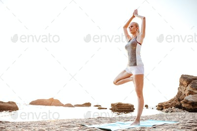 Young woman standing in yoga pose on one leg