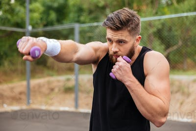 Young bearded sports man doing workout with small dumbbells