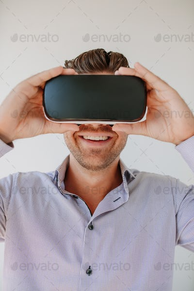 Young man using VR goggle and smiling.