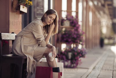 Woman With Shopping Bags Sitting On Bench. Shopogolic Concept.