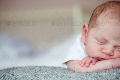 Newborn baby boy lying on bed, sleeping, close up
