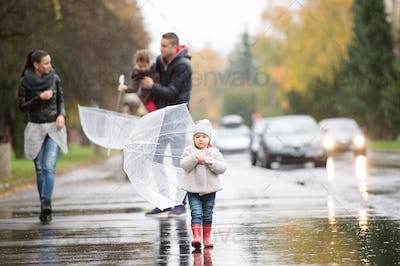 Family with daughters under the umbrellas. Walk on rainy day.