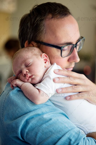 Close up of young father holding his newborn baby son