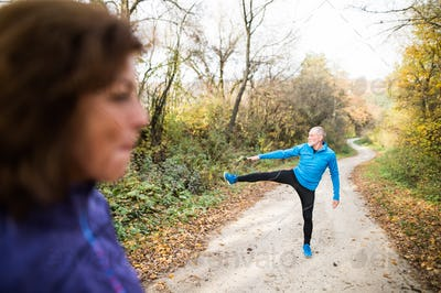 Senior couple running outside in sunny autumn forest, stretching