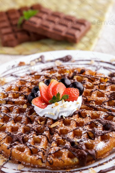 homemade waffle with chocolate, strawberry, and cream topping