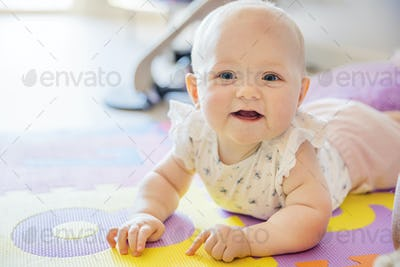 Smiling baby girl with blue eyes playing on floor mate