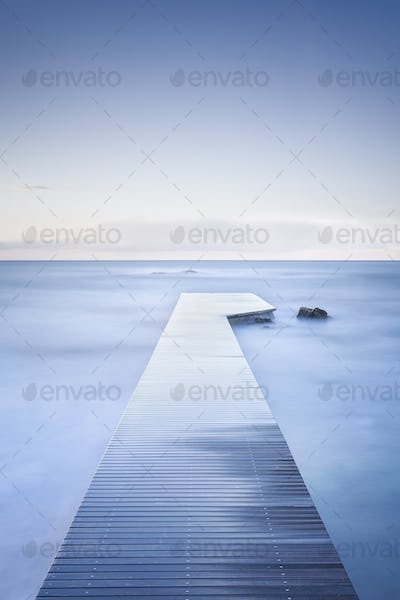 Wooden pier, rocks and calm sea on long exposure.
