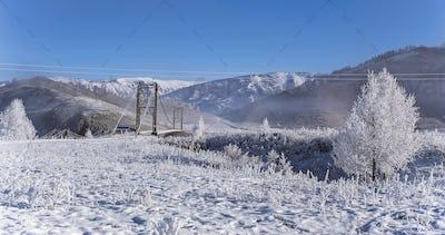 Snowy bridge on foggy winter frosty morning