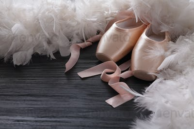 Pink ballet pointe shoes and feather on black wood background