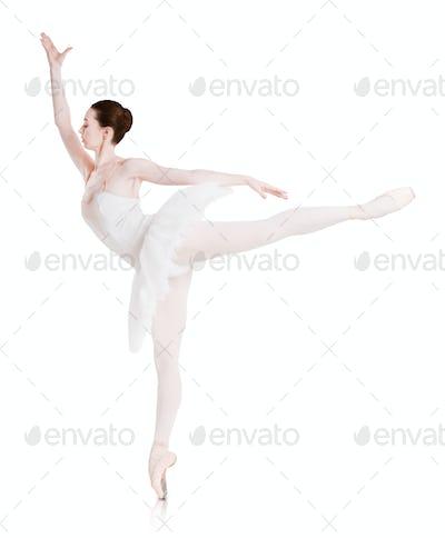 Ballerina makes ballet position arabesque isolated on white background