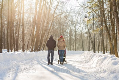 parents carry the baby in a stroller through the snow
