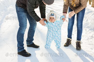 first steps of little baby boy in winter park