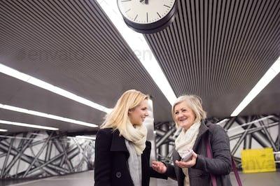 Two beautiful women standing at the underground platform, talkin
