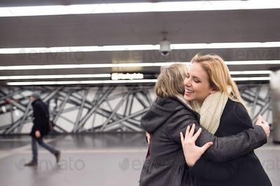 Two beautiful women standing at the underground platform, huggin