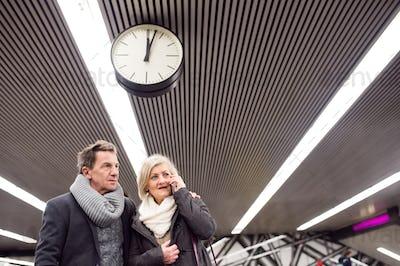 Senior couple standing at the underground platform, calling