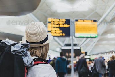 Woman backpacker at the airport checking flights