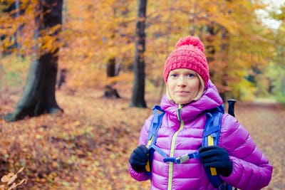 Hiking woman with backpack looking at camera in inspiring autumn