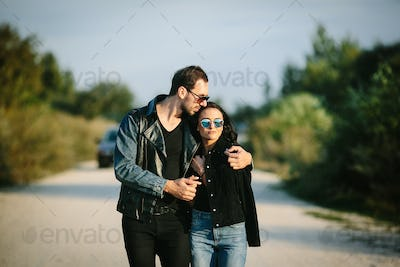 Young happy romantic couple walking along road