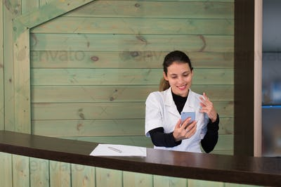Woman in a spa recpetion uses tablet pc texting to client. Beauty and technology concept.